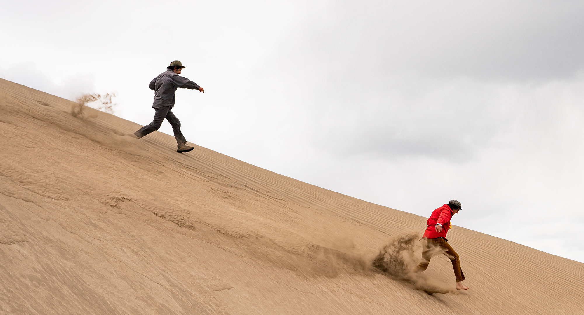 Two men running down a sand dune at Christmas Valley Sand Dunes