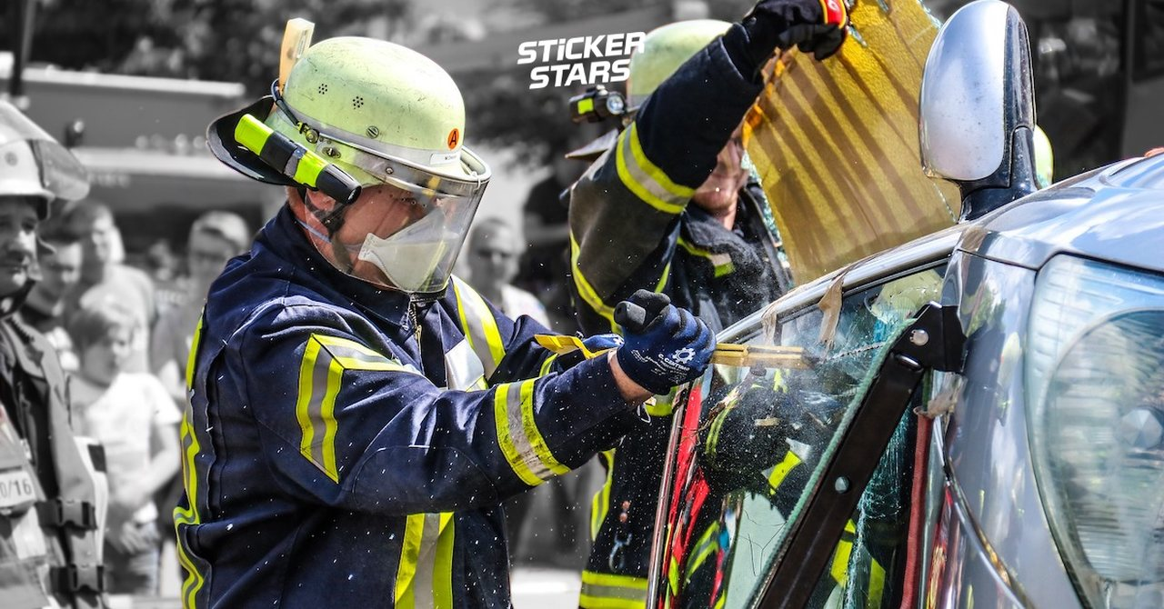 Zwei Feuerwehrleute zeigen auf einem Feuerwehrfest, wie man Menschen aus einem Autowrack befreit