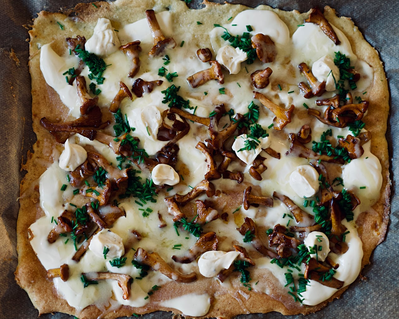 A pizza topped with chanterelle, cheese, mayo, and chive.
