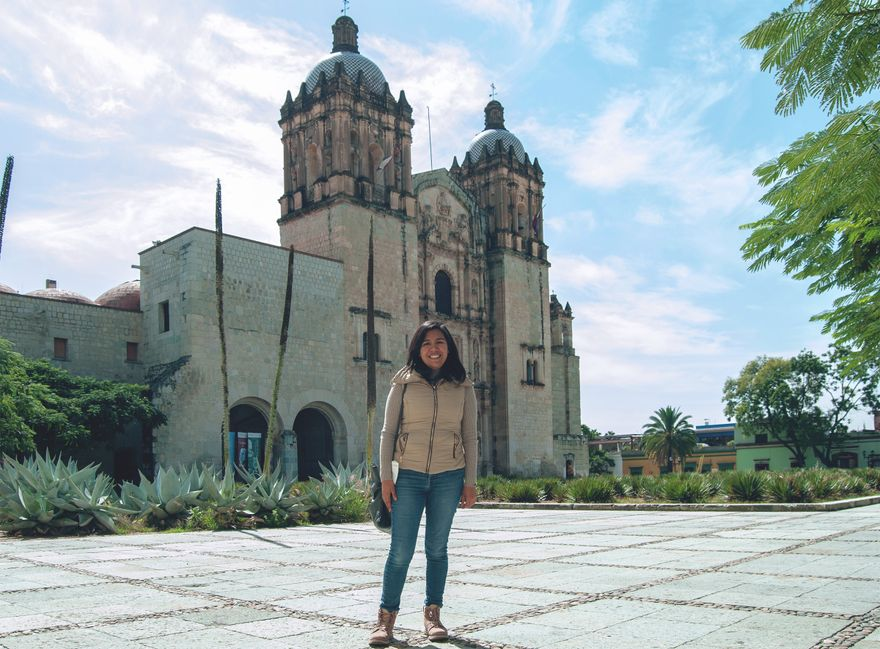estrella, wearing jeans and a puffy vest, stands smiling in front of santo domingo in oaxaca on a sunny day