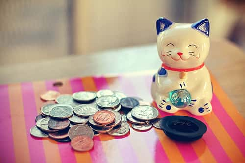 japanese porcelain cat with coins on table