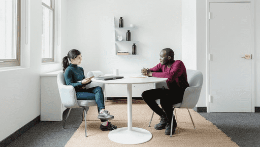 Two colleagues have discussion over white round table in room with rug, shelves, cupboard. Person takes notes on notebook with pen and has staff wellbeing business discussion