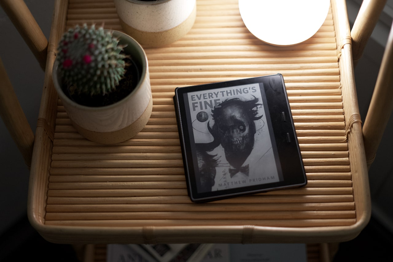 An e-reader on a tray, showing the cover of a short story, named Everything's Fine. It's illustrated with a skull wearing a tie. A tiny planet, maybe Earth, orbits around the head. The author's name at the bottom reads Matthew Pridham.