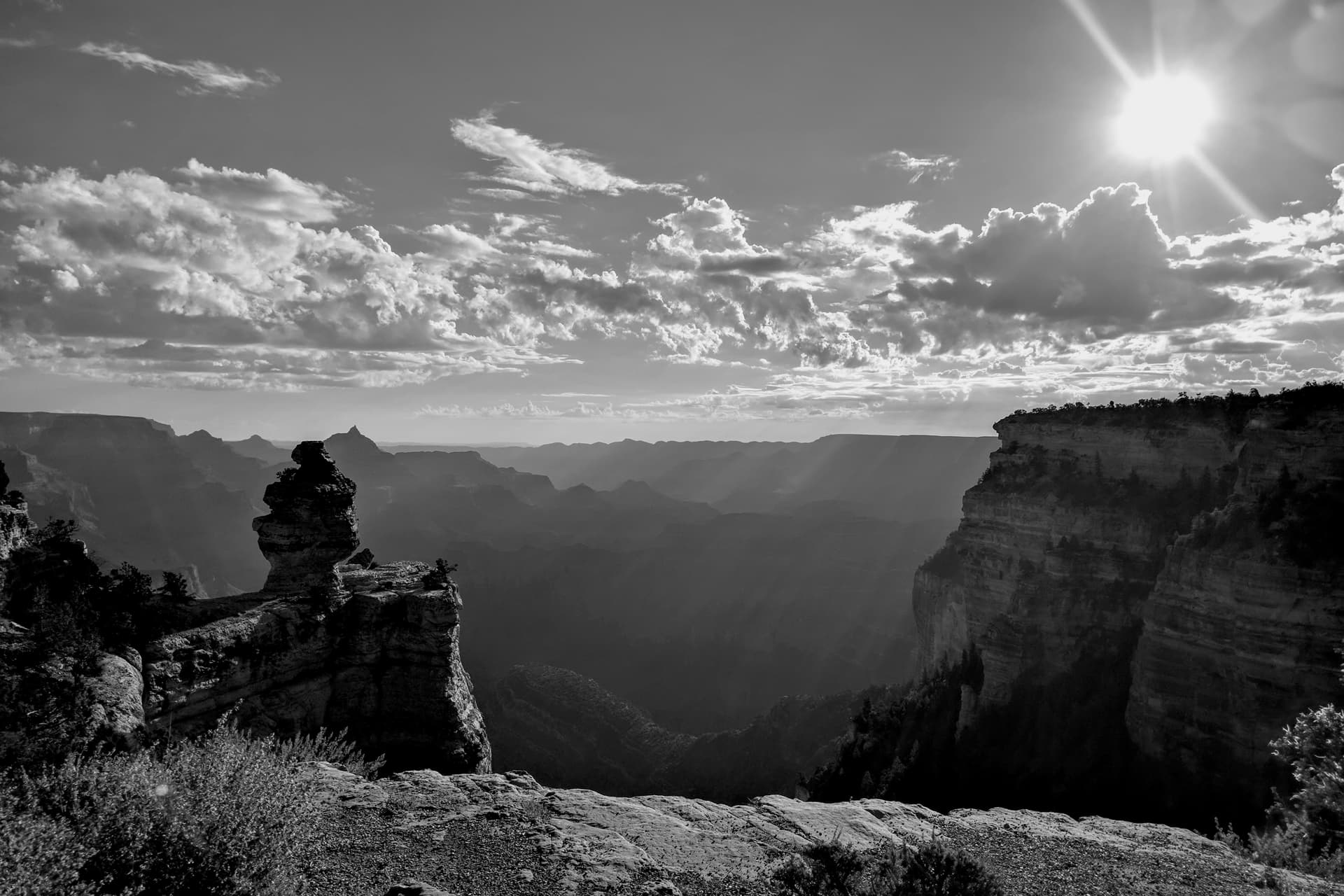 A black-and-white photograph of the Grand Canyon shortly after dawn. Thick haze obscures the far side of the Canyon. In the foreground, a pillar of rock rises out of the South Rim.