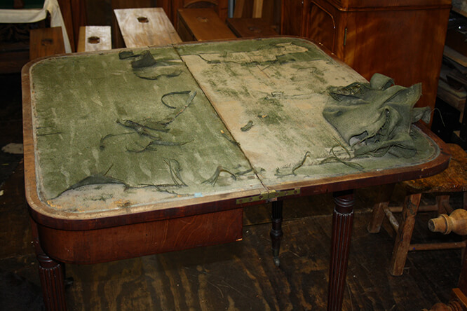 TABLE WITH DAMAGED BAIZE