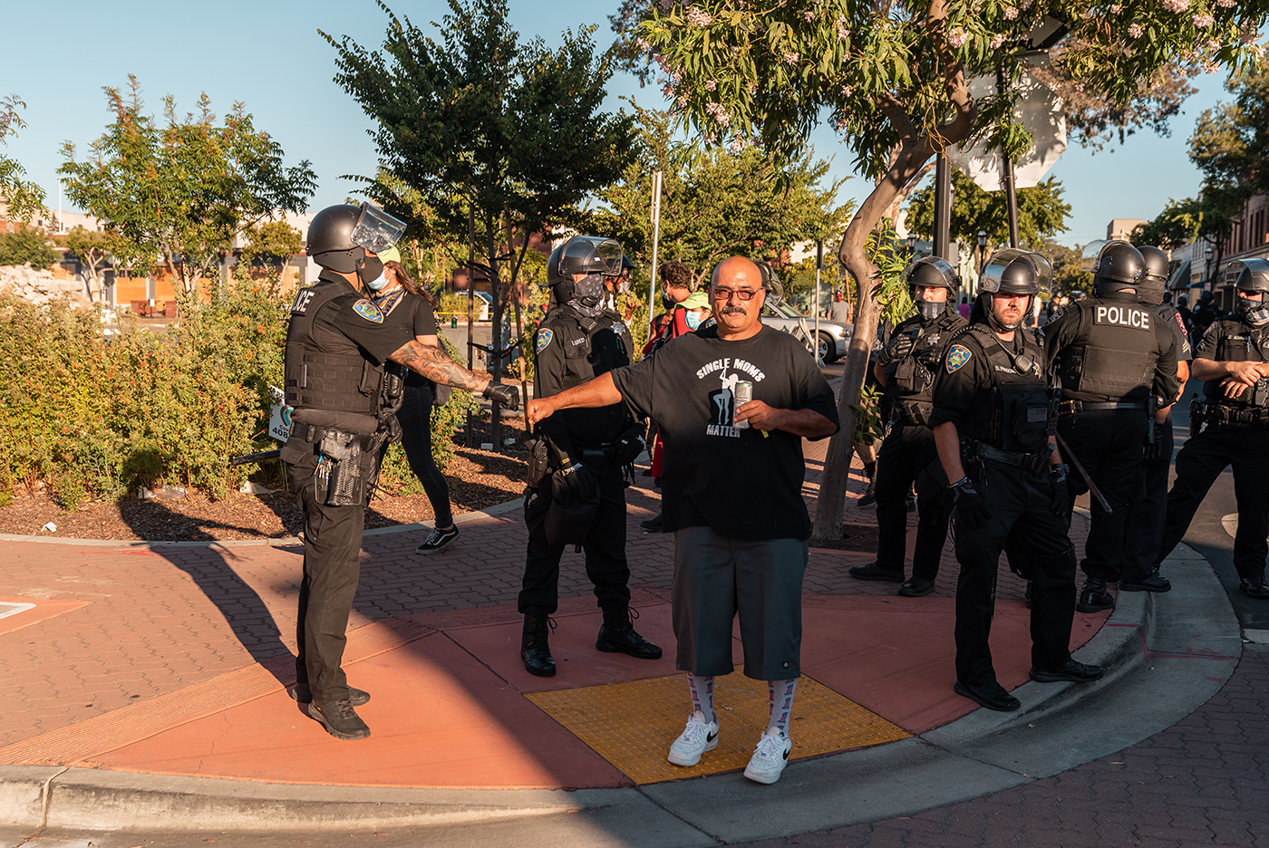 "A counter-protester wearing a shirt that reads ""Single Moms Matter"" and depicting a dancer on a pole gives a fist bump to police officers while drinking in Martinez, Calif., on Sunday, July 12, 2020."