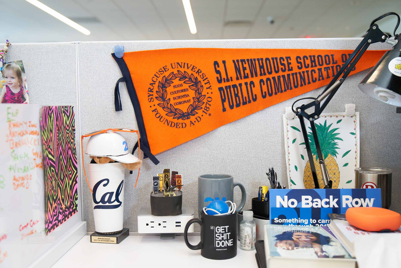 A 2U employee's desk with a Syracuse pennant, Cal University cup, and other novelty items