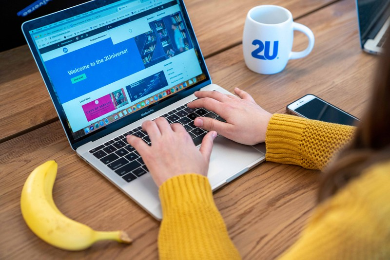 Woman on her laptop browses the 2Universe website with a 2U coffee mug and banana next to her