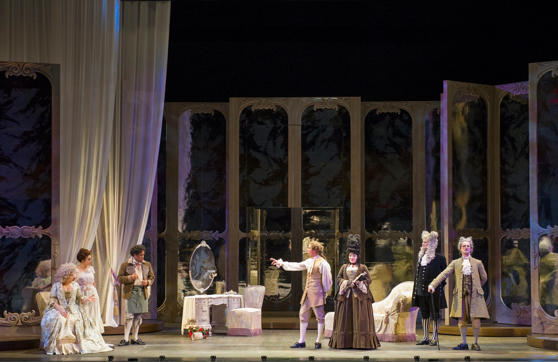 Opera players in 18th century attire scattered across boudoir furnishing in front of towering revolving doors and white swag draperies.