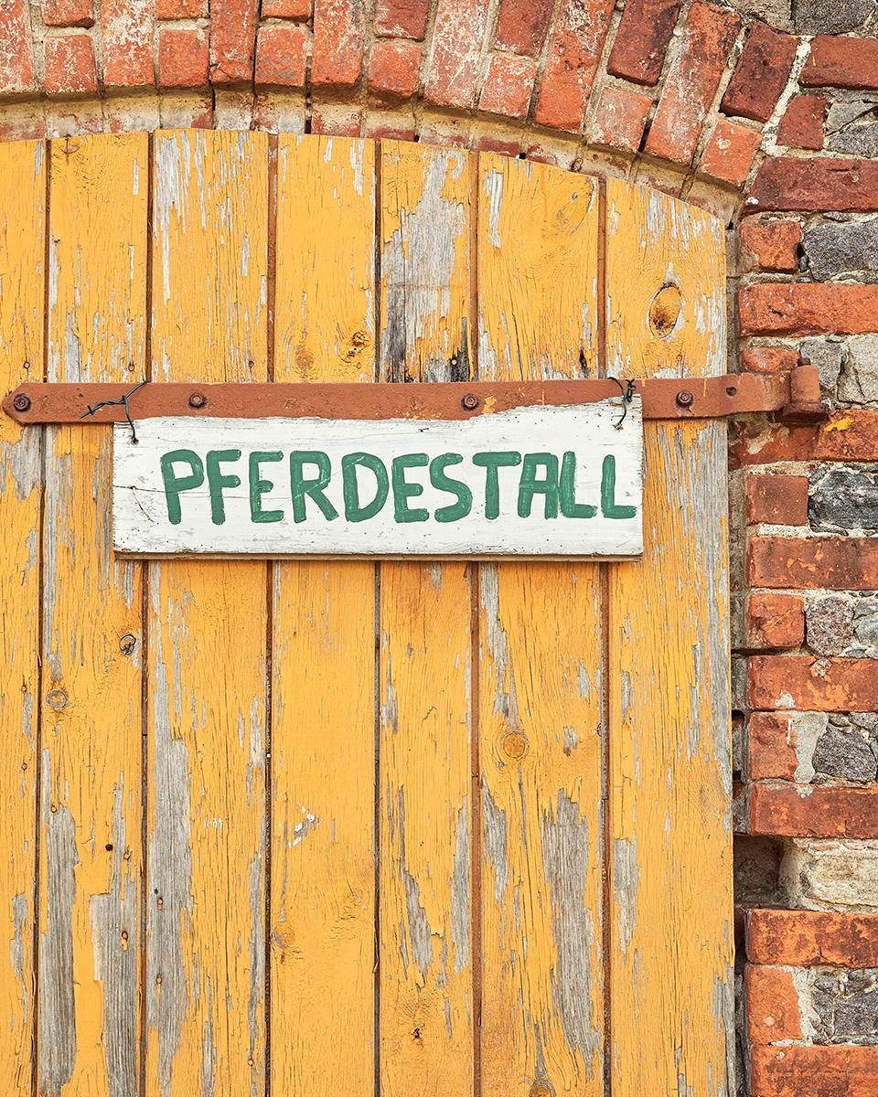 Ein Schild an einer Tür das auf einen Pferdestall hinweist