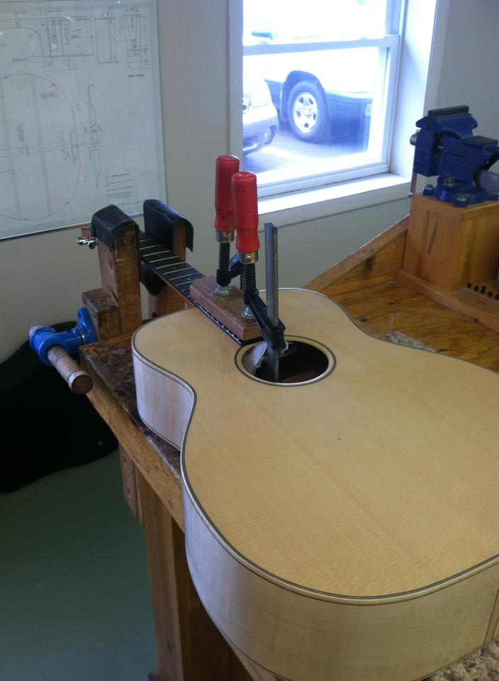 Image of a half built acoustic guitar on a workbench with a clamp on the guitar's neck