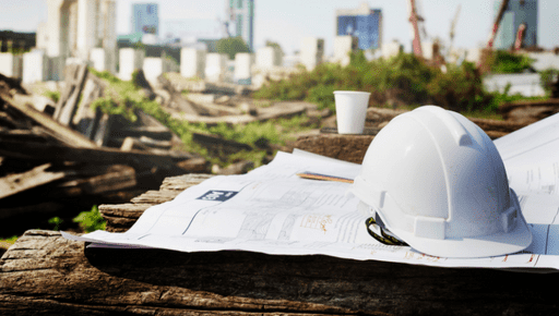 Builder's hat sits on construction plans on wood with tea coffee cup. with construction site in the background. Business uses top KPI #KeyPerformanceIndicator