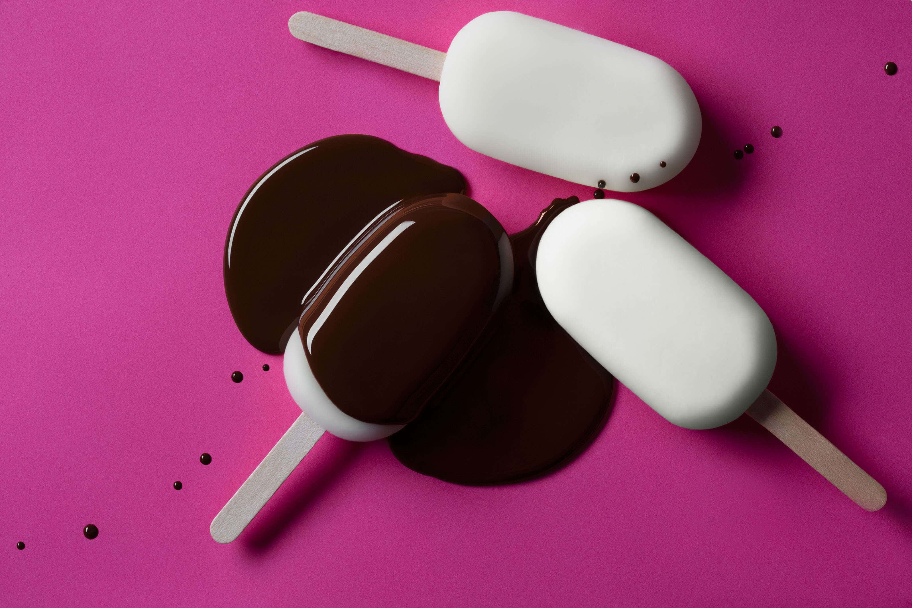 magnum ice cream lollies on pink background with chocolate poured over