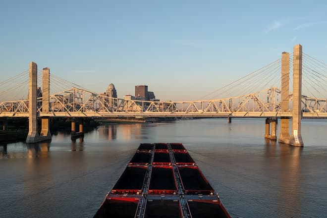 An empty coal barge approaches downtown Louisville on the Ohio River. In front of it, a brutalist suspension bridge of white steel and concrete pylons.