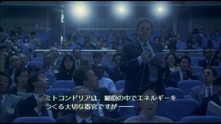 An audience member at a talk before Asakura's stands up and asks a series of questions. It looks as though he is reading the script