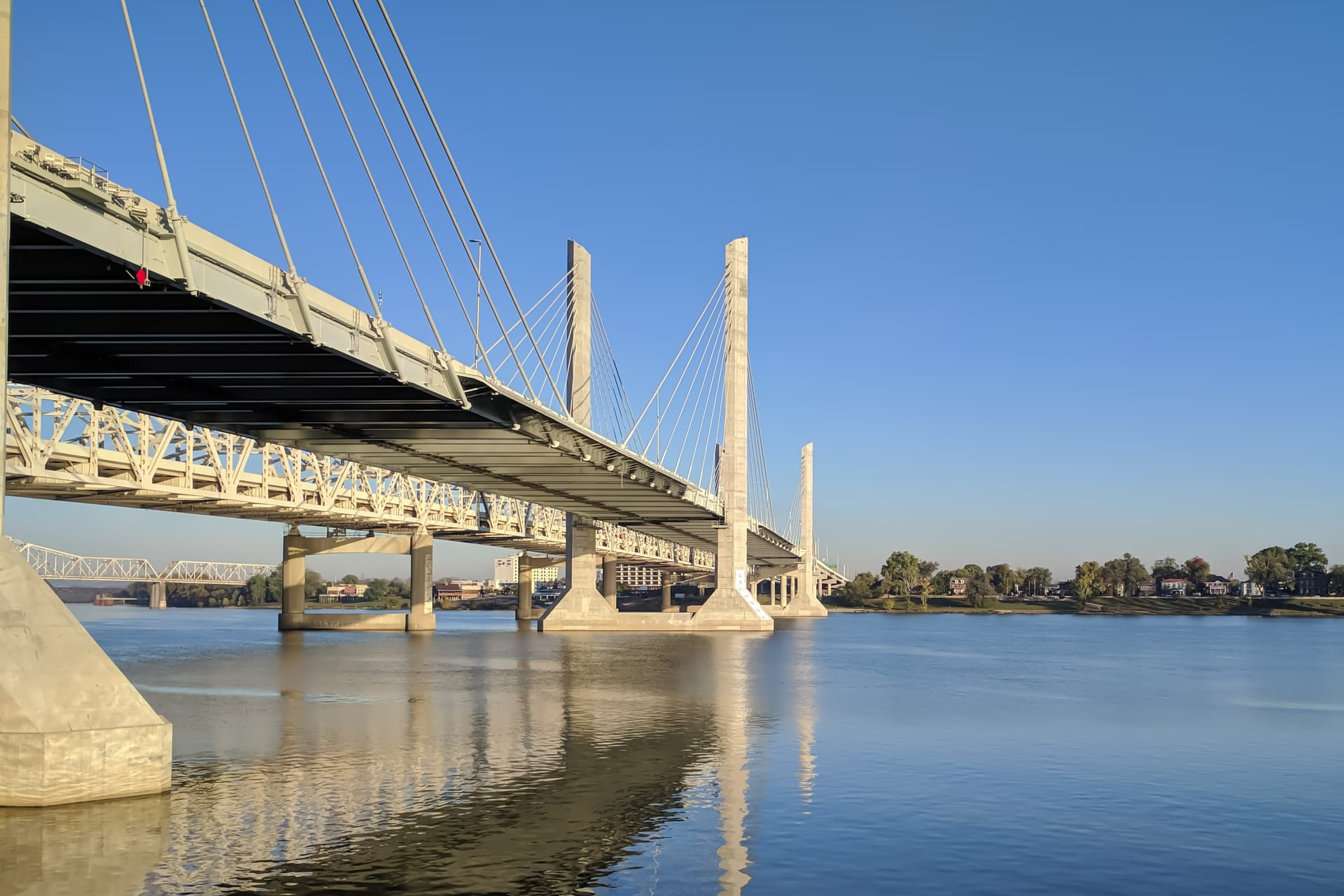 A photograph of a brutalist suspension bridge of white steel and concrete pylons crossing the Ohio River.