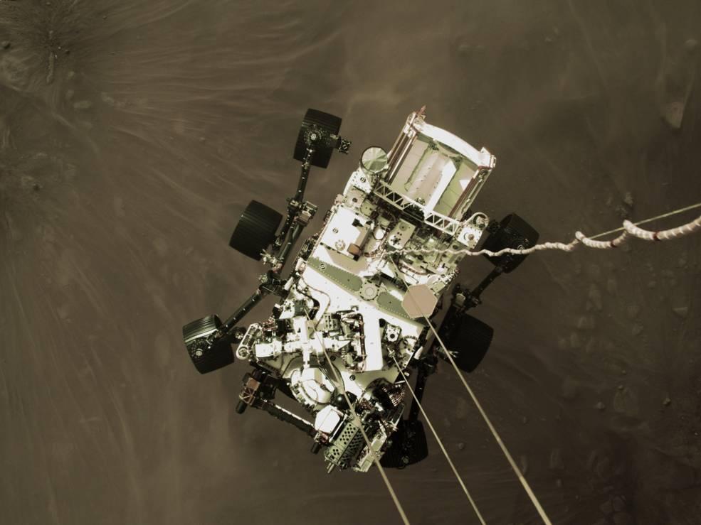 Imaginea 1: Roverul Perseverance, aflat la aproximativ 2 metri de suprafața planetei Marte, aflat la câteva secunde de desprinderea de macaraua spațială (Sursa foto: NASA)
