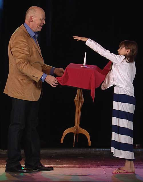 A child helps Brad make a table float on stage