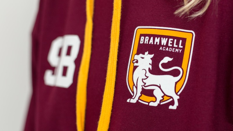 A close-up of a leavers hoodie with the academy logo printed on the front left chest
