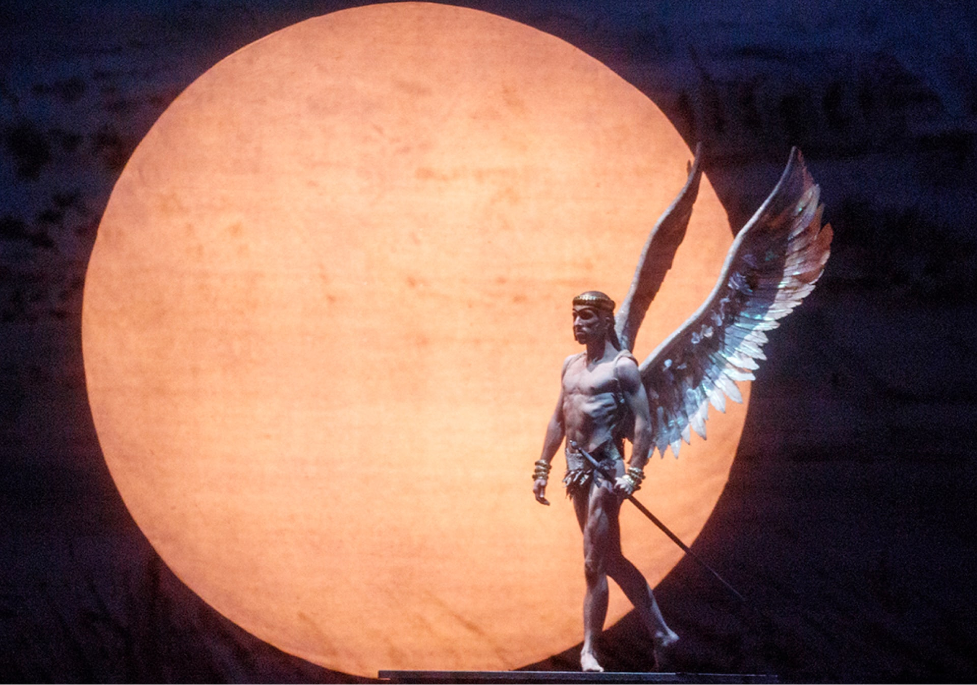 Bare-chested dancer with giant wings and sword stands in front of huge orange moon.
