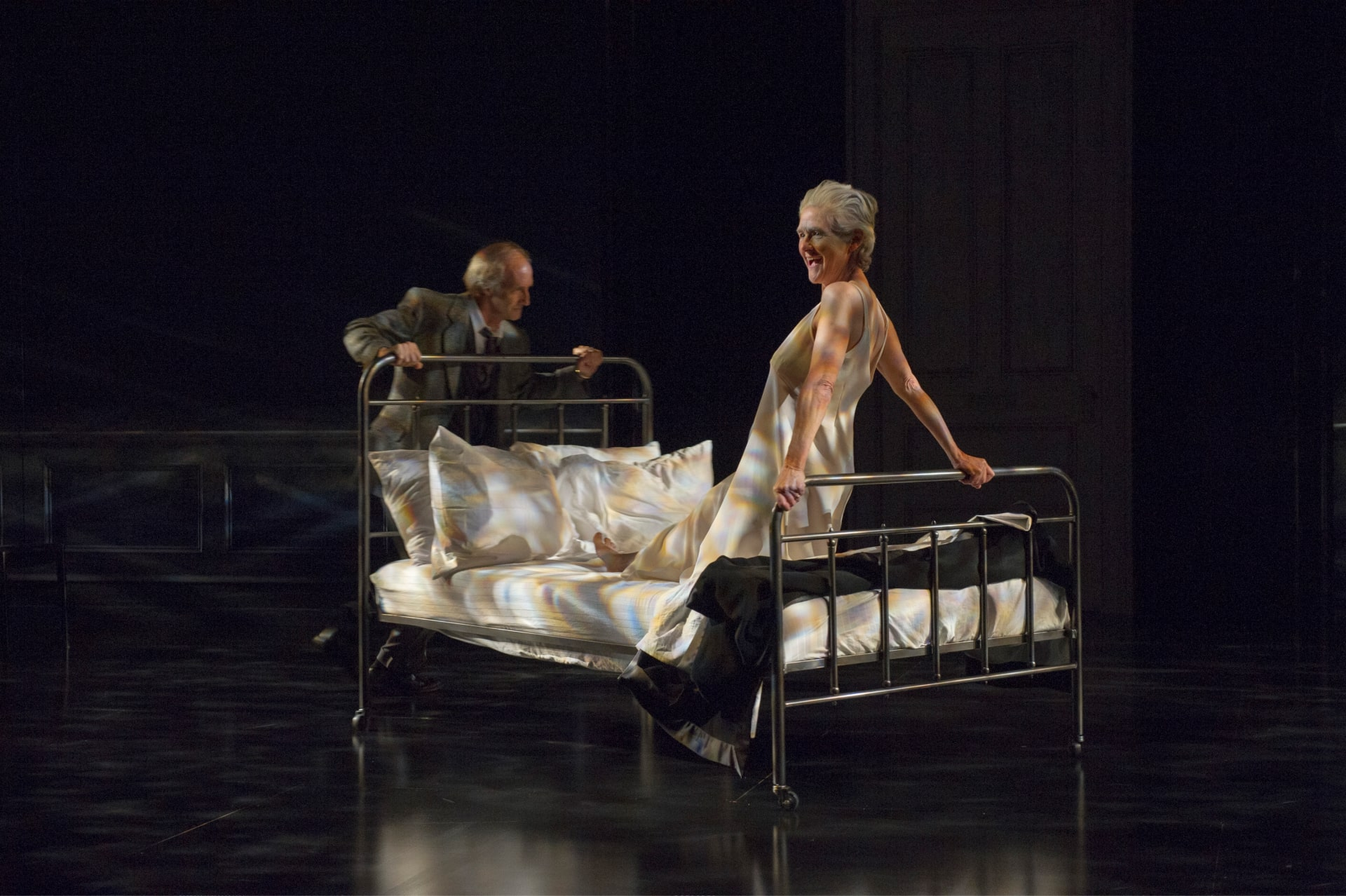 Woman in white slip clasps footrail of bed as man in suit spins bed around stage under dappled light.