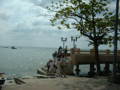 ... am Strand von Ban Hua Thanon. Sie folgen ihrem Thaiführer, der erstaunlich gut Deutsch spricht. Ansonsten sind sie aber typische Touristen. Einer fotographiert den Müll und schüttelt anschlie?end missbilligend den Kopf, eine tatscht dem Führer auf den Rücken und fragt sicherlich weltbewegende Fragen und erklärt ihm, dass es auf Mallorca auch mal so warm war aber keine Wolken und einer kuckt den Thaifrauen und Kindern hinterher.