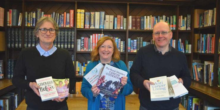 Alan Sterenberg, former Suffolk Libraries CEO Alison Wheeler and stock librarian Brandon King with some of the books from the new cancer collection.