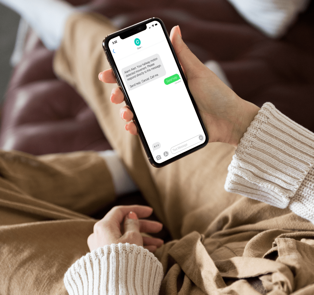 Woman holding phone reading Cove alarm messages