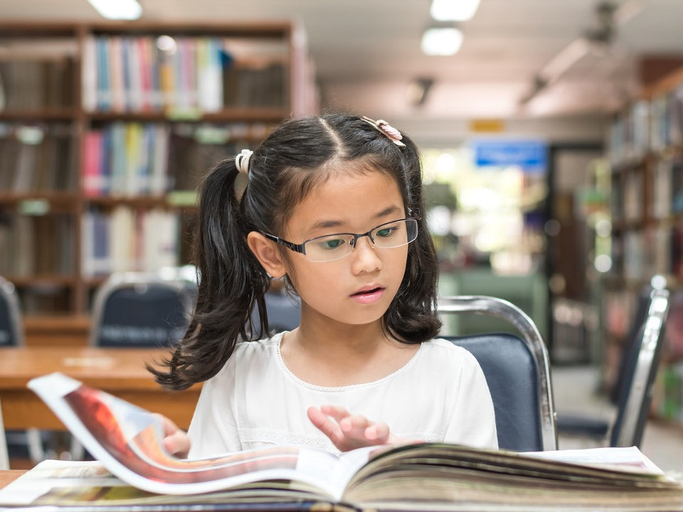 A girl looking at a book, she's seated in a library