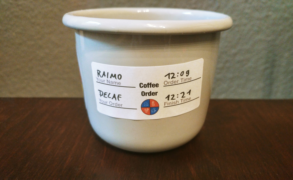 The cup we used for Coffee Kanban with an order sticker on it that has the name of the customer, their order, the start and finish time on it.