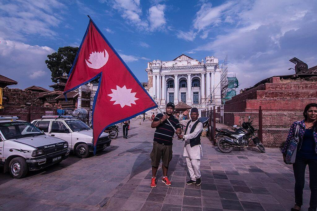 Flag of Nepal and two Nepalese holding it.