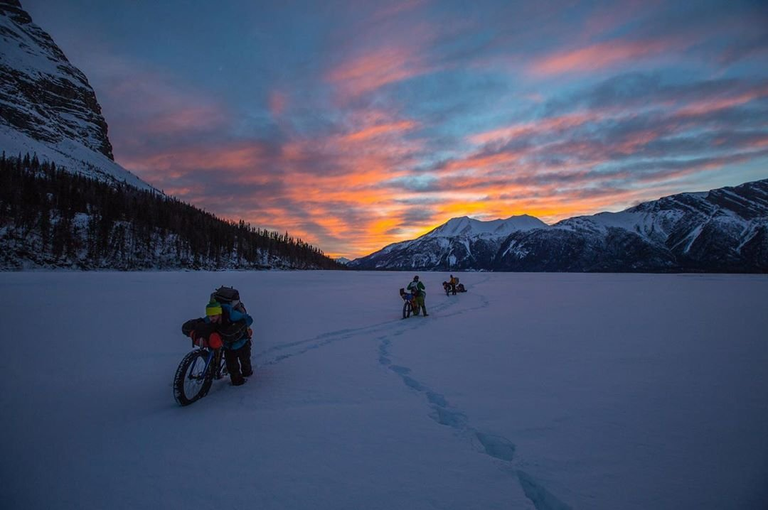 A few extreme outdoor cyclists packing their bikes through a frozen, snow covered tundra
