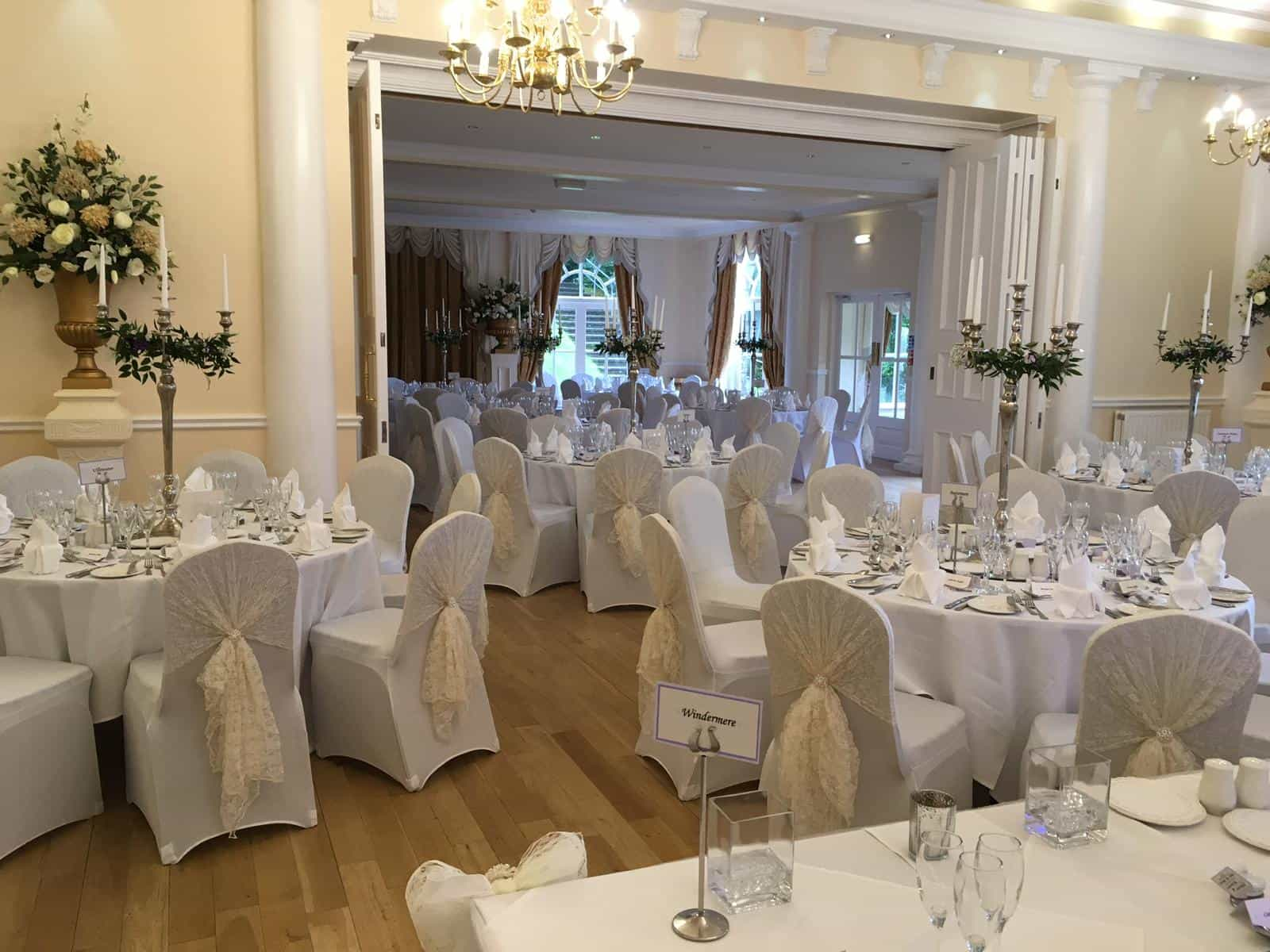 Wedding breakfast venue dressing with white chair and table linen and white lace hoods over chairs