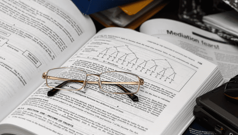 Glasses sit on accountancy book, textbook, as business owners need to understand accounting #business