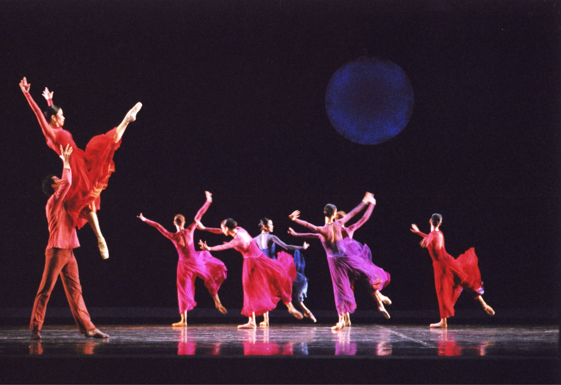 Dancer holds ballerina in red modern outfit aloft, in front of chorus of ballerinas against black sky with blue full moon.