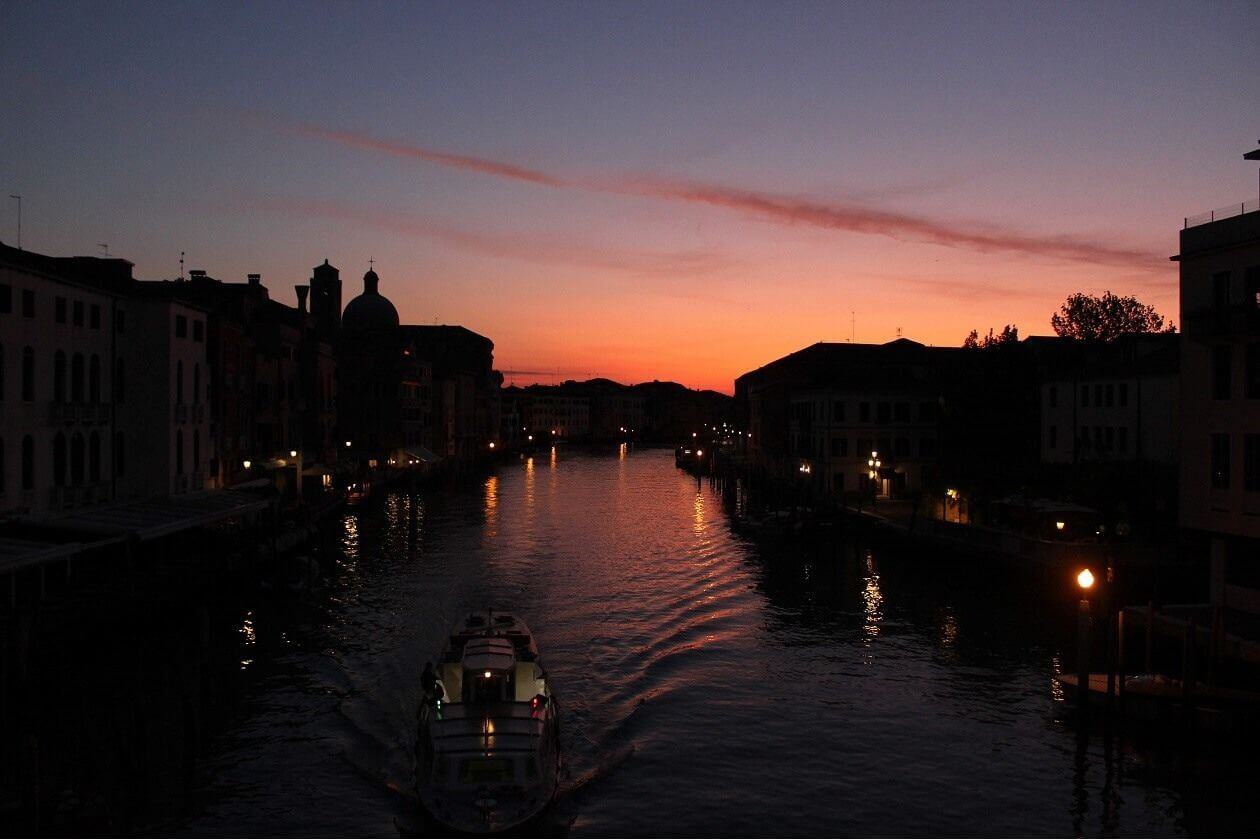 Ein Boot fährt über einen Kanal in Venig bei Sonnenaufgang.