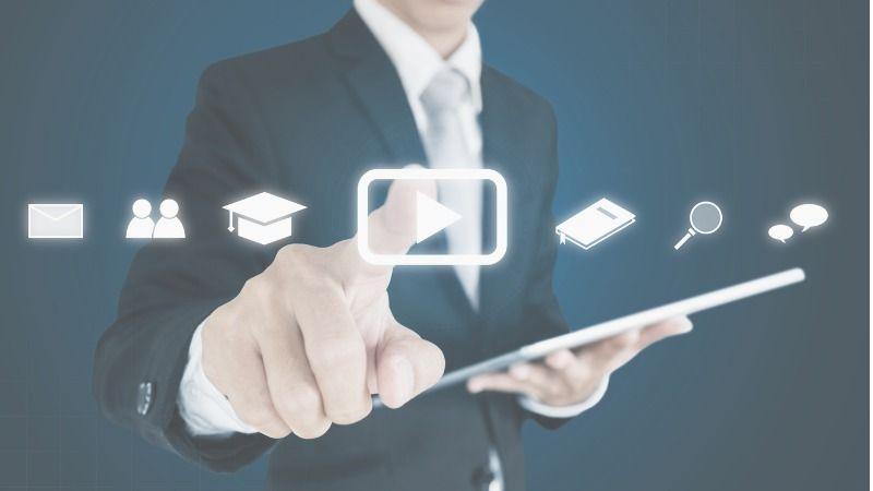 Ein Mann im Anzug mit einem Tablet-Computer berührt ein Symbol in einer Reihe mehrere leuchtender, freischwebender Symbole.