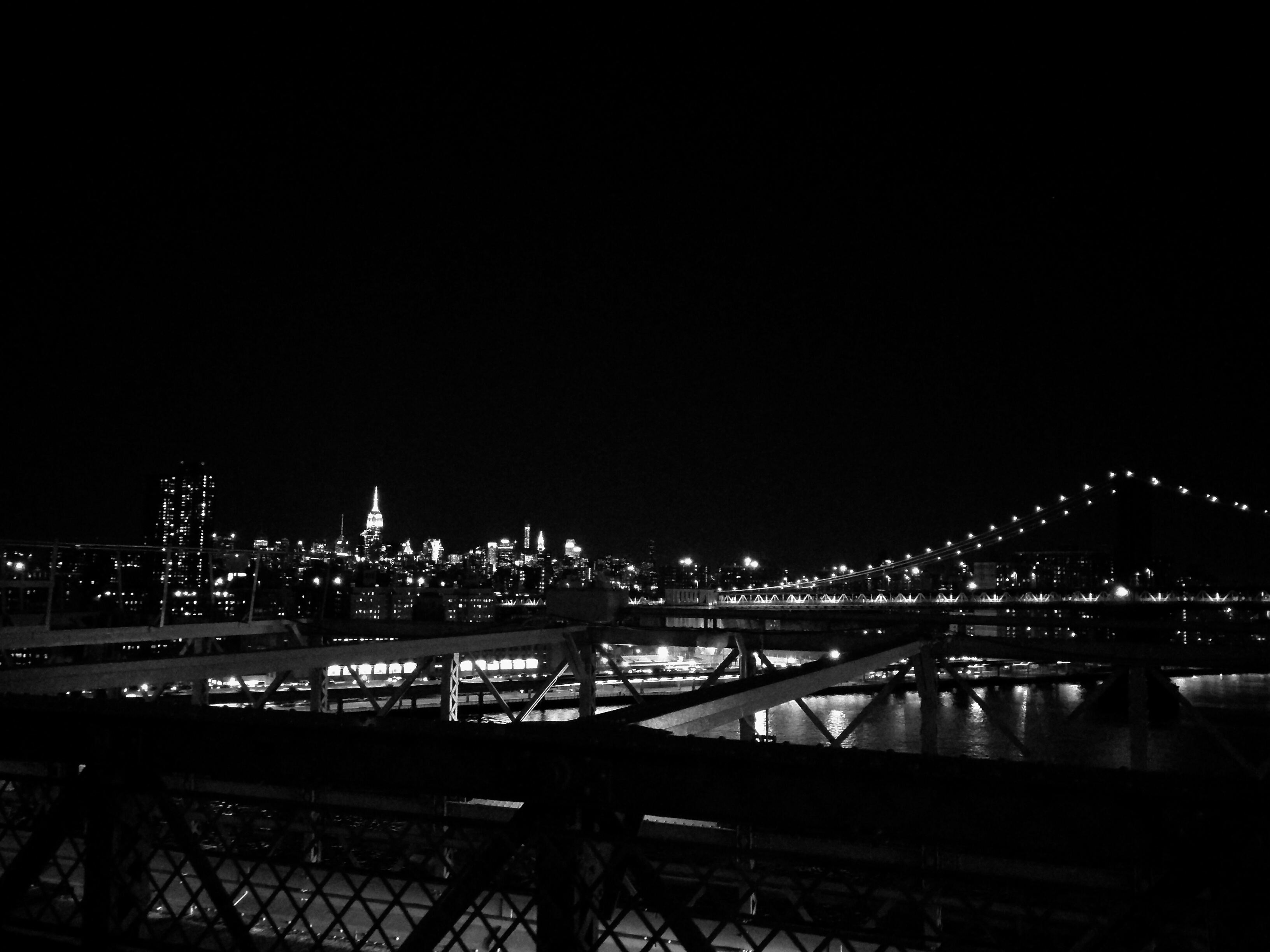 Brooklyn bridge with Manhattan in the distance. Black and white filter applied.