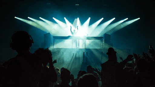 Performers stand on stage above a crowd with blue lighting and smoke effects at a rave part, disco, club, concert