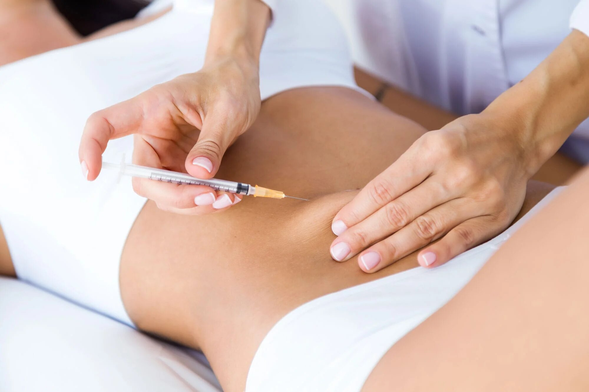 Female patient receiving needle injection in her abdominal section