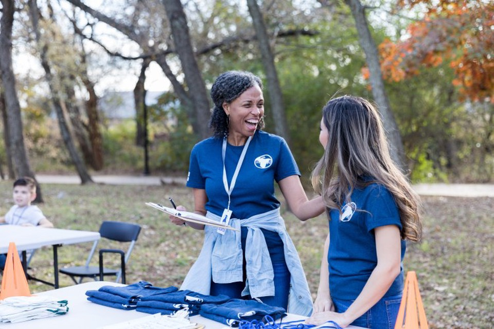 Social worker in leadership position mentors volunteer at outdoor event for a nonprofit organization.