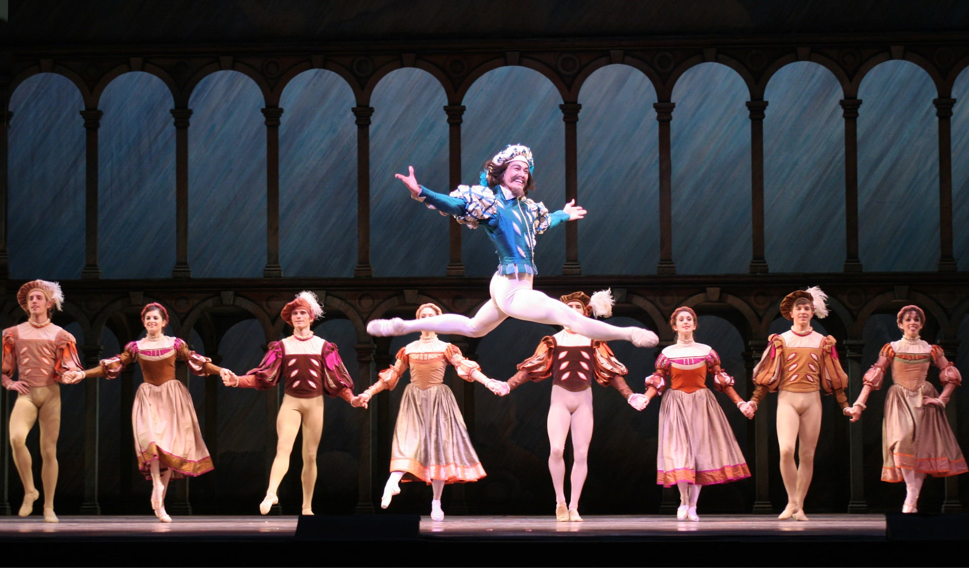 Bearded dancer in puffy blue jacket and hat leaps, watched by village dancers in front of levels with arches against painted blue sky.
