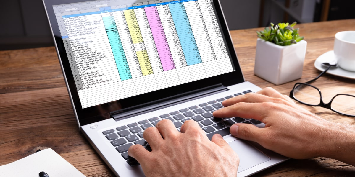 A pair of hands typing on a laptop keyboard, with a spreadsheet of structured data on the screen