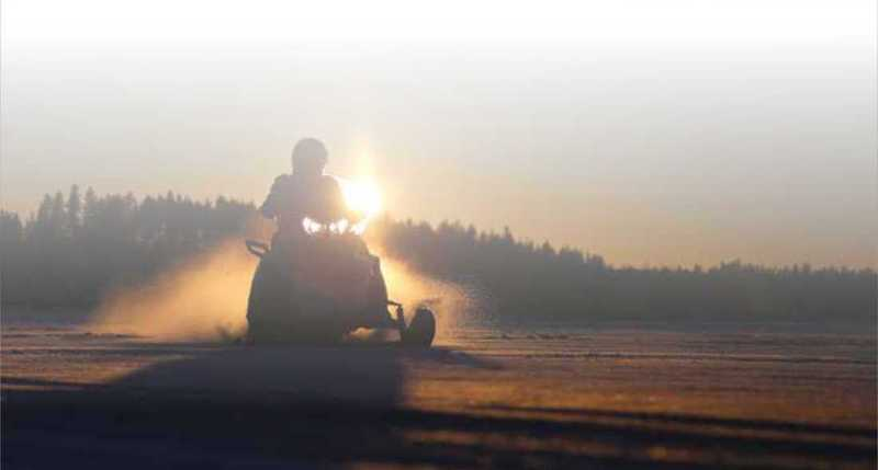 Snowmobiler riding at sunset