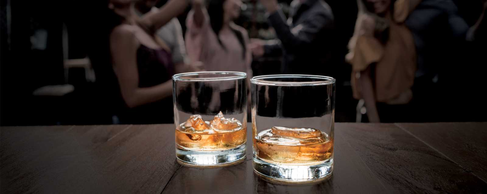 Belfour Spirits image of young group dancing with whiskey glasses on polished would in the foreground