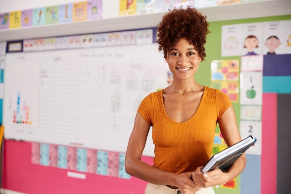 A smiling teacher in her classroom.
