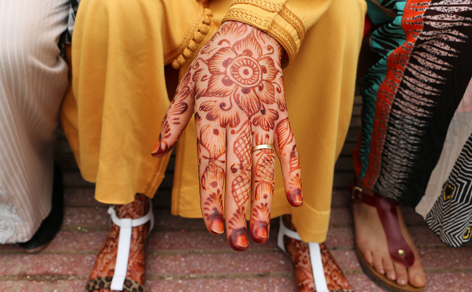 a woman's hands displaying red henna tattoos