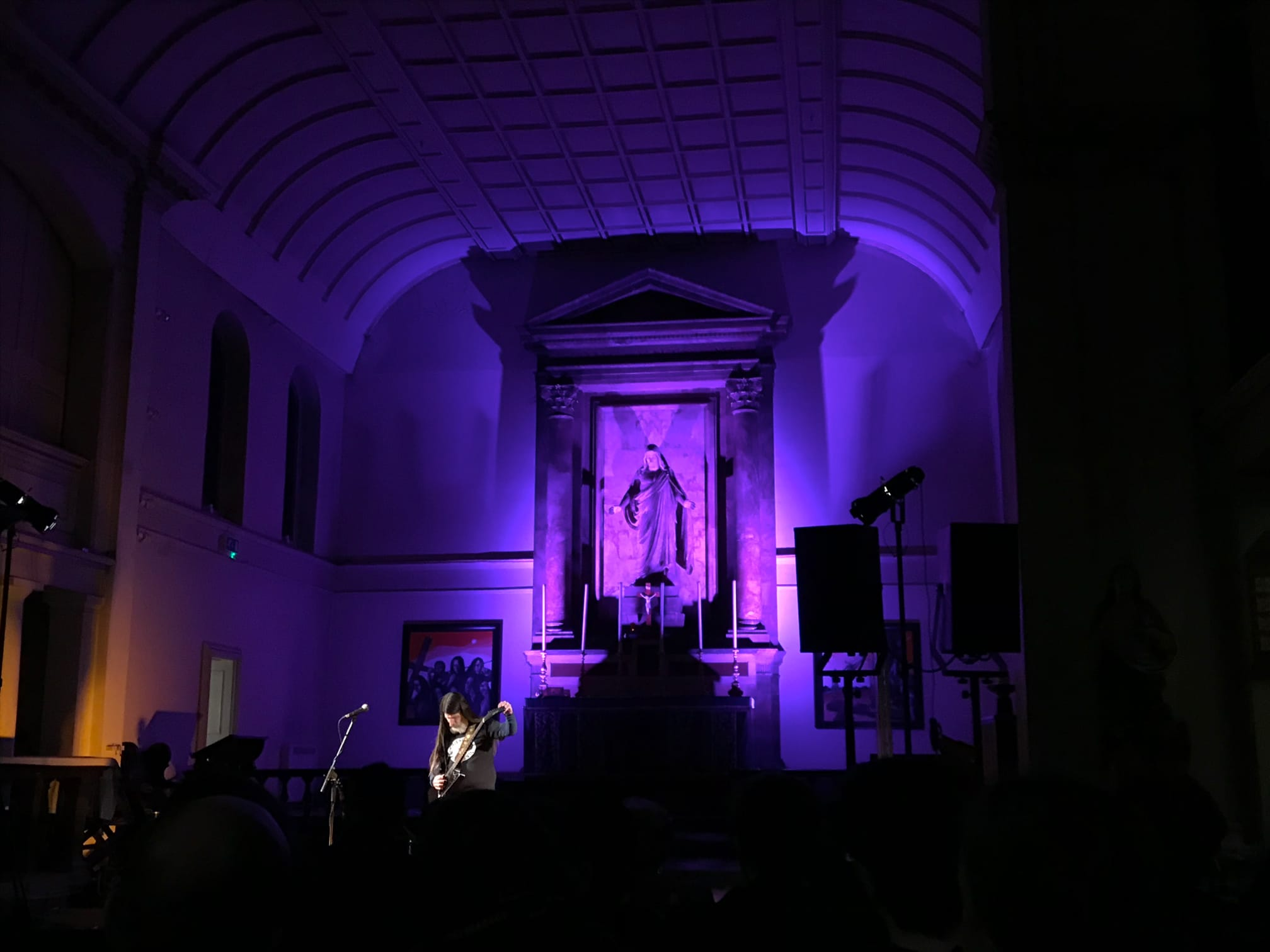 Dylan Carlson tuning his guitar in front of the altar at St John of Bethnal Green church, bathed in purple floodlights