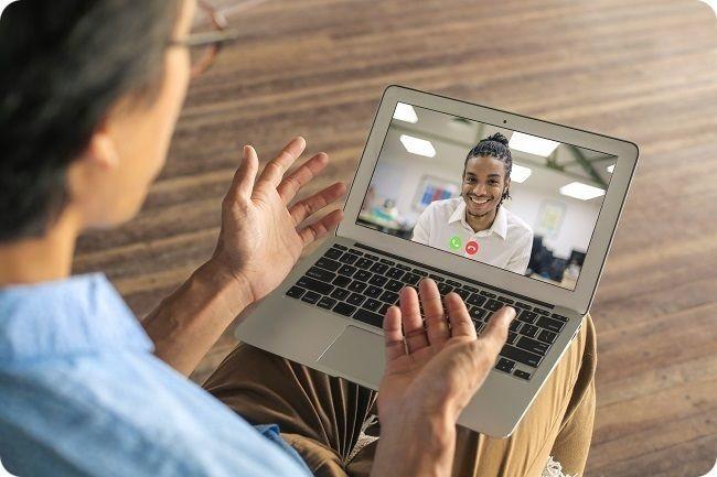 une personne échange avec une autre personne en video conference, son ordinateur portable sur les genoux