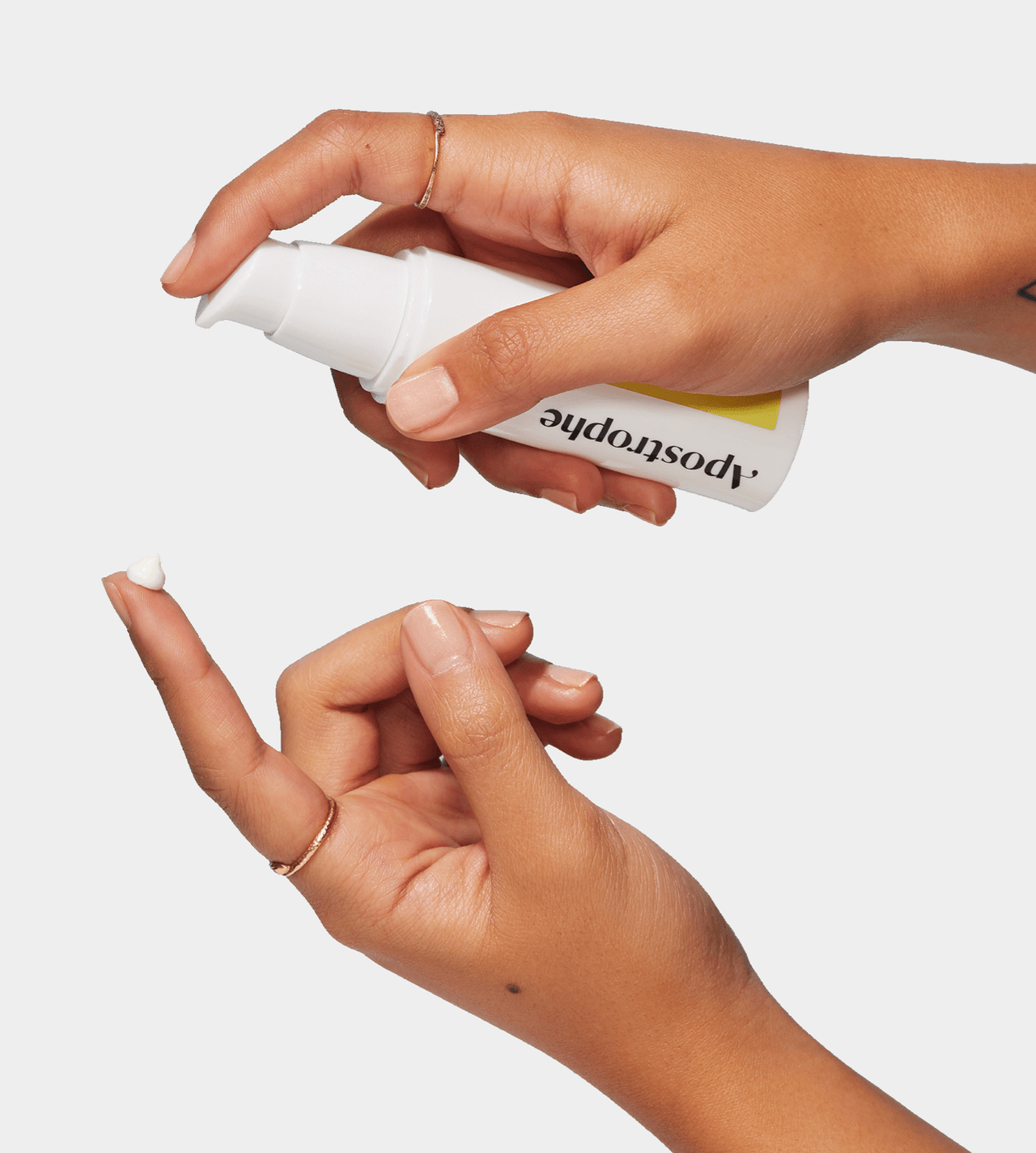 Two hands, one holding an Apostrophe bottle dispensing white topical cream onto the other hand.